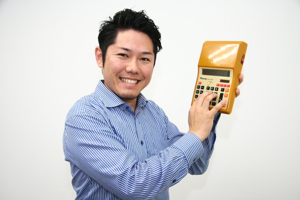 電卓をたたくCOZYの田上さん