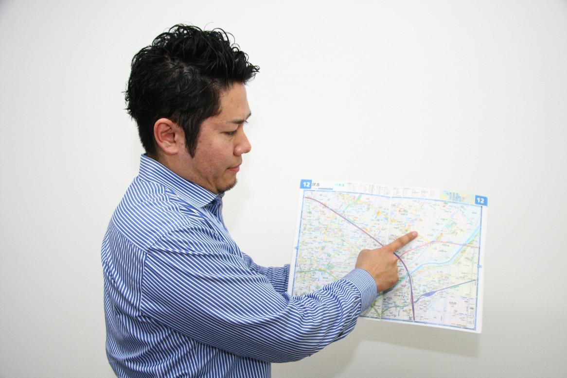 地図で説明するCOZYの田上さん