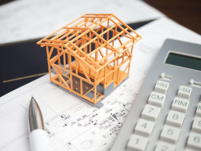 建築中の家の模型と電卓